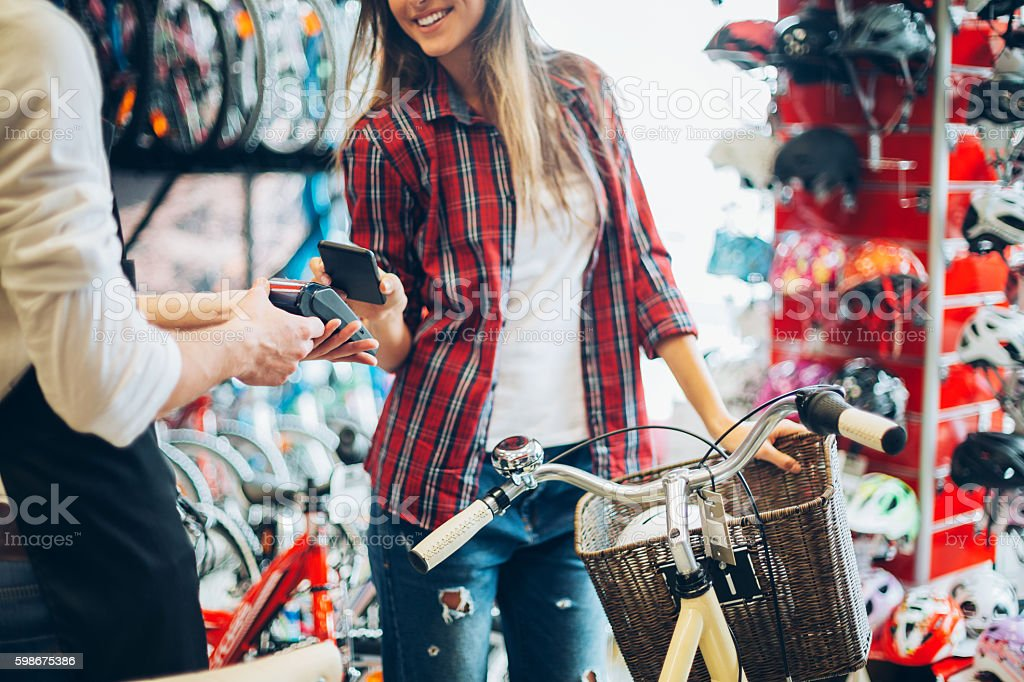 Smart phone contactless payment in bike shop stock photo