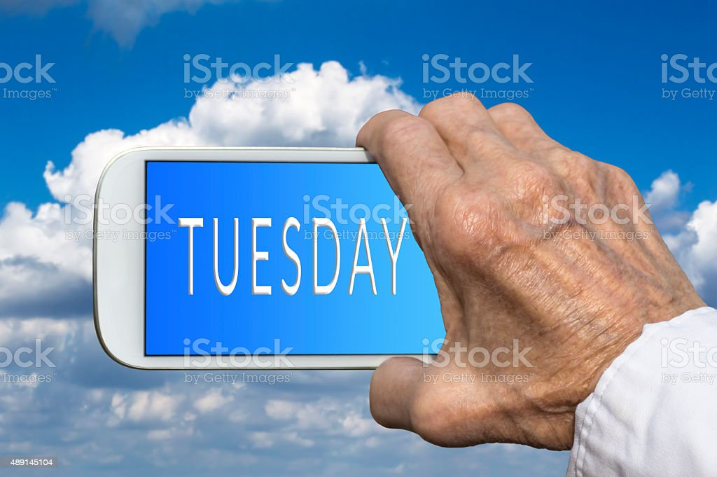 Smart phone in hand with days of the week. Tuesday stock photo