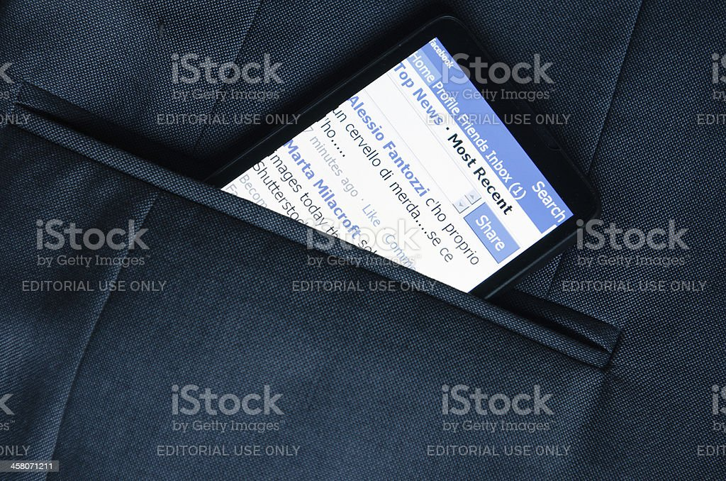 Smart phone with Facebook application in the pocket royalty-free stock photo