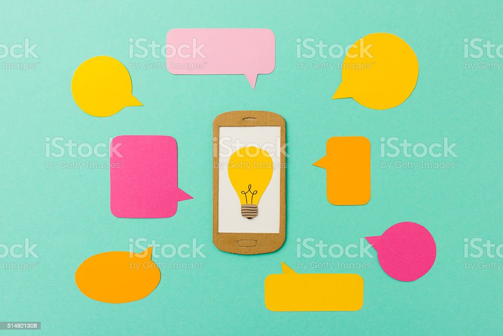 Smart phone with light bulb symbol and talk bubbles stock photo