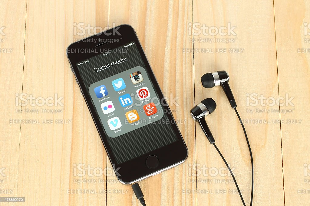 Smart phone with social media logos on screen and headphones stock photo