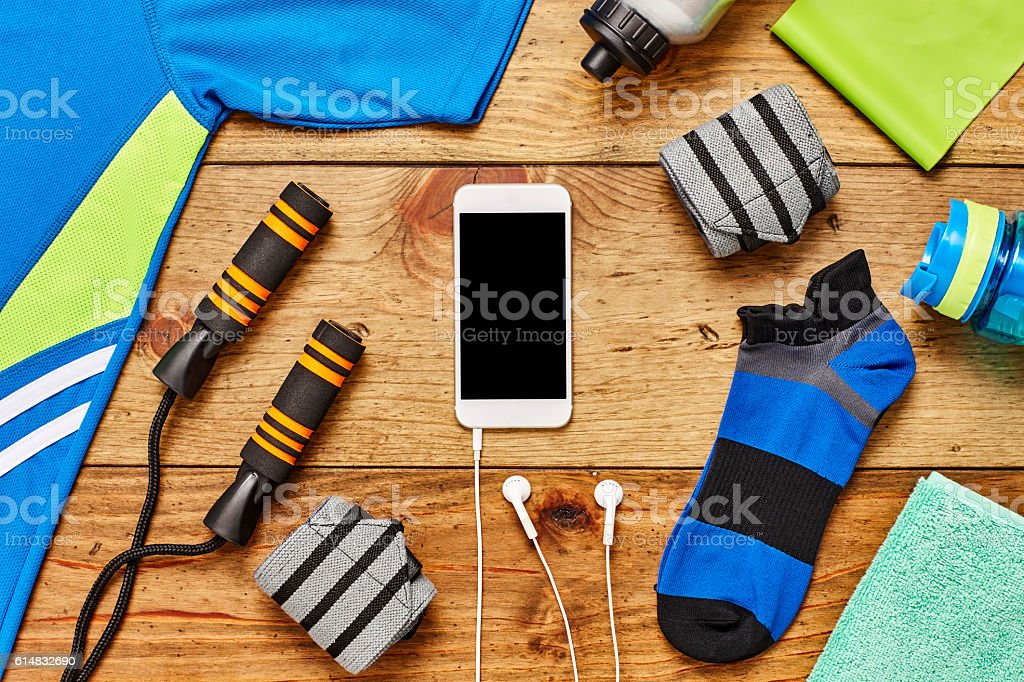 Smart phone with sports equipment and headphones on hardwood floor stock photo