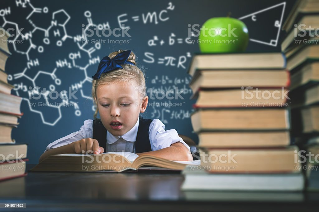 Smart school girl reading a book at library stock photo