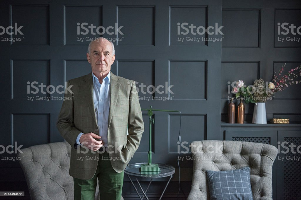 Smart senior man in grey wood panelled living room stock photo