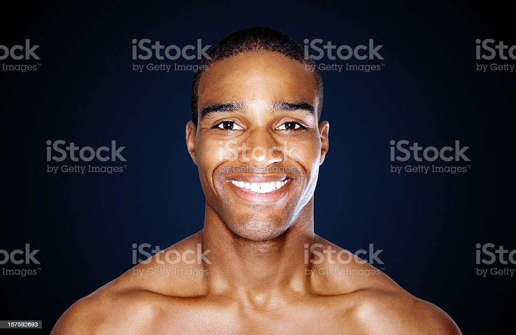 Smart shirtless man smiling isolated against black royalty-free stock photo