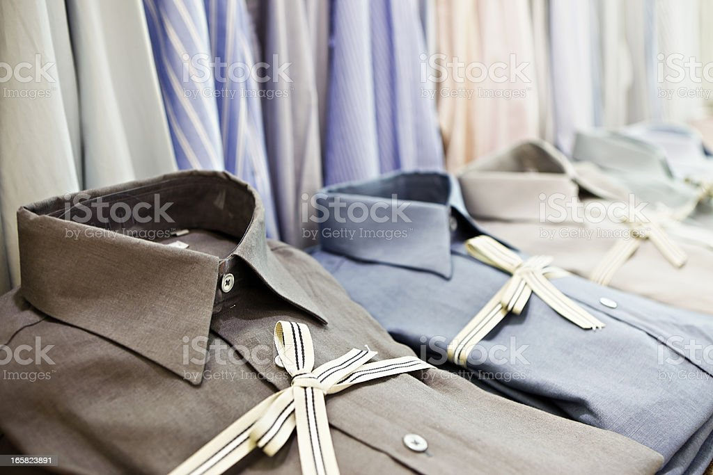 Smart shirts tied with striped ribbon in exclusive menswear store royalty-free stock photo
