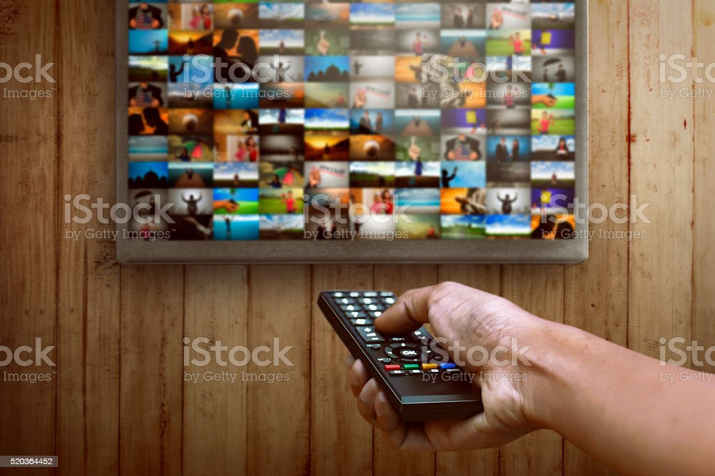 Smart tv and hand pressing remote control stock photo