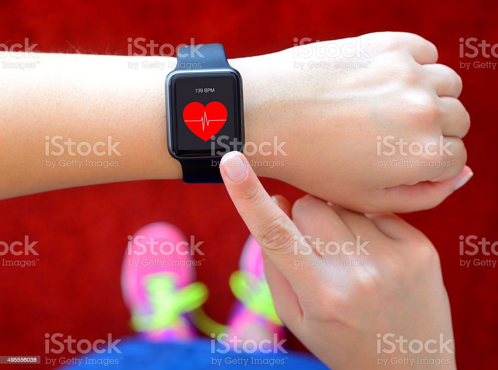 Smart watch displaying heart rate while exercising stock photo