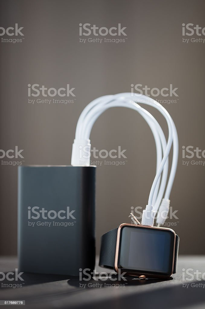 Smart watch on a charge with power bank external battery stock photo