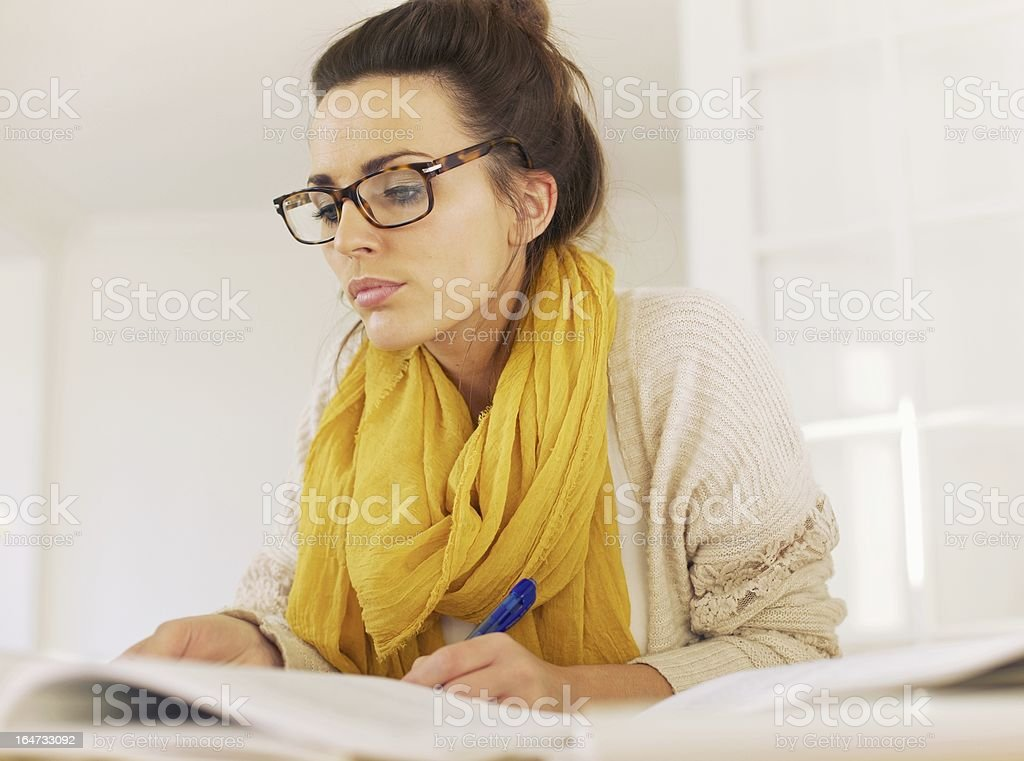 Smart Woman Reading While Taking Notes royalty-free stock photo