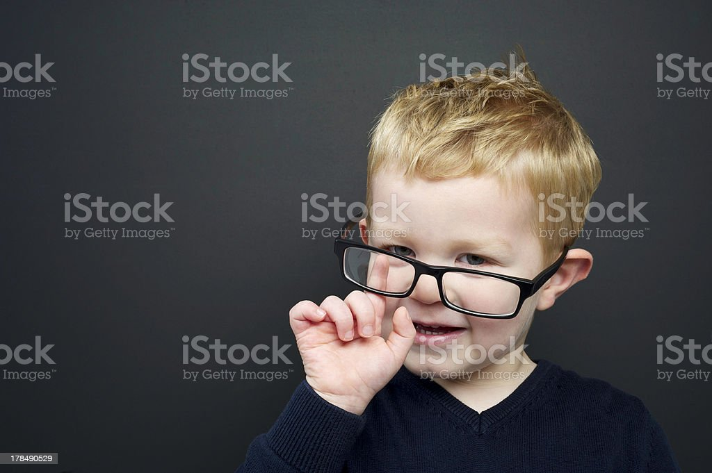 Smart young boy stood infront of a blackboard royalty-free stock photo