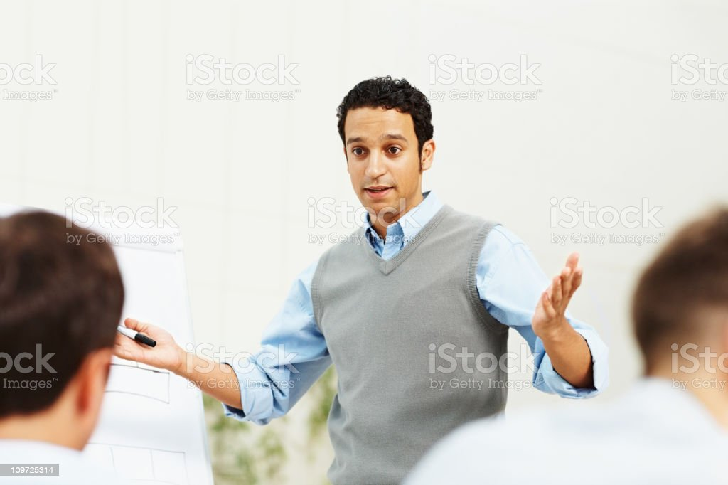 Smart young business man giving a presentation to team royalty-free stock photo