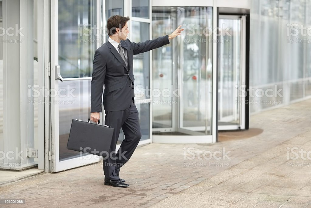 Smart young businessman hailing a taxi cab royalty-free stock photo