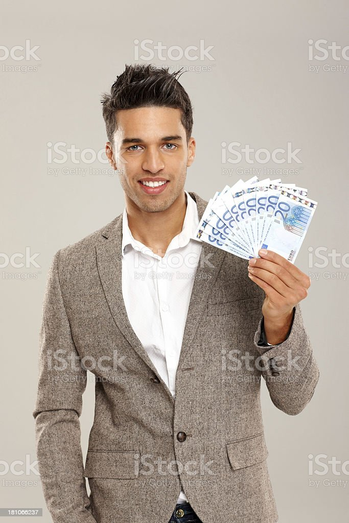 Smart young businessman holding Euro banknotes royalty-free stock photo