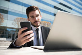Smart young businessman using smartphone and laptop computer