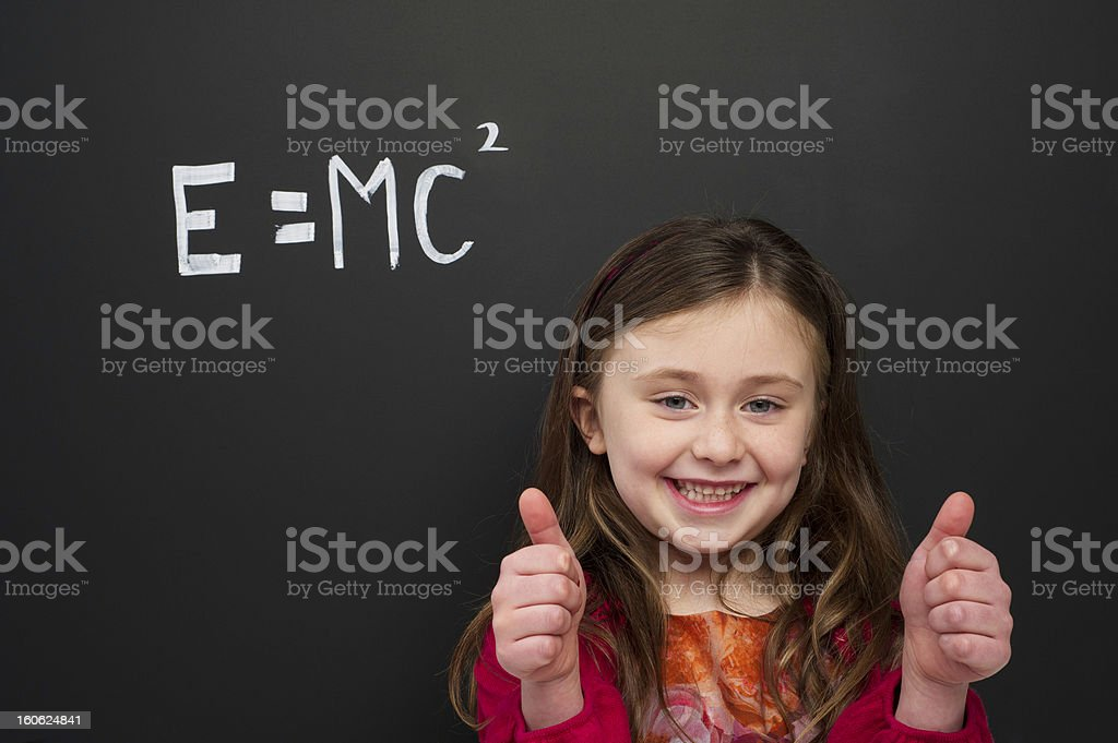 Smart young girl stood infront of a blackboard stock photo