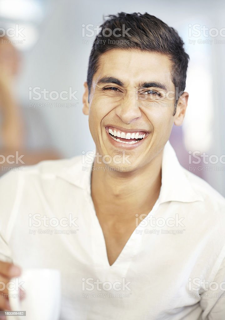 Smart young laughing man drinking a cup of coffee royalty-free stock photo