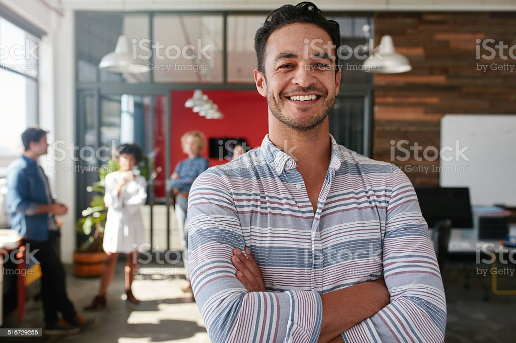 Smart young male designer with his colleagues in background stock photo