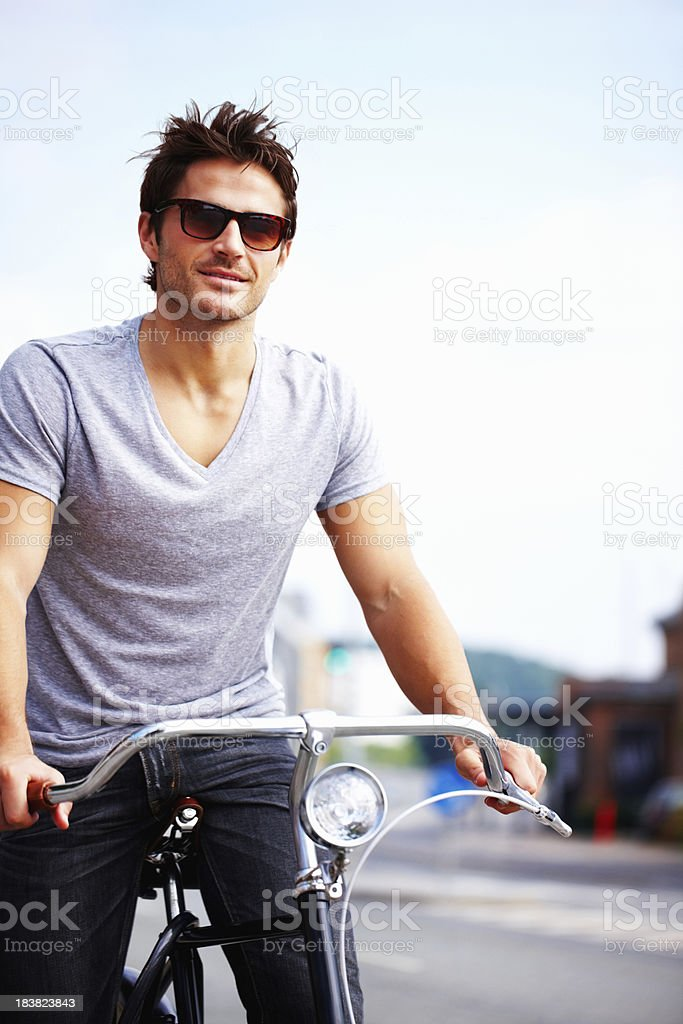 Smart young man wearing sunglasses riding a bicycle royalty-free stock photo