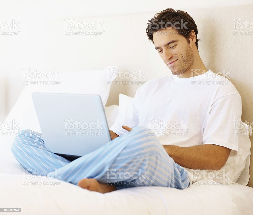 Smart young man working on laptop while in a bedroom royalty-free stock photo