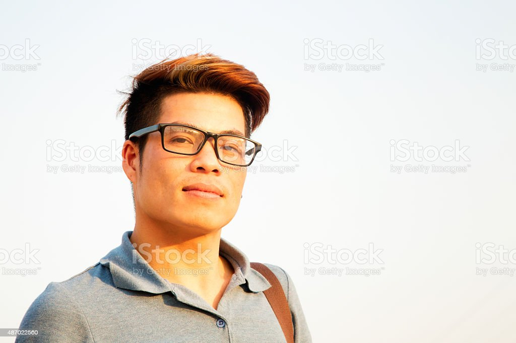 Smart young Vietnamese student wearing glasses outdoors stock photo