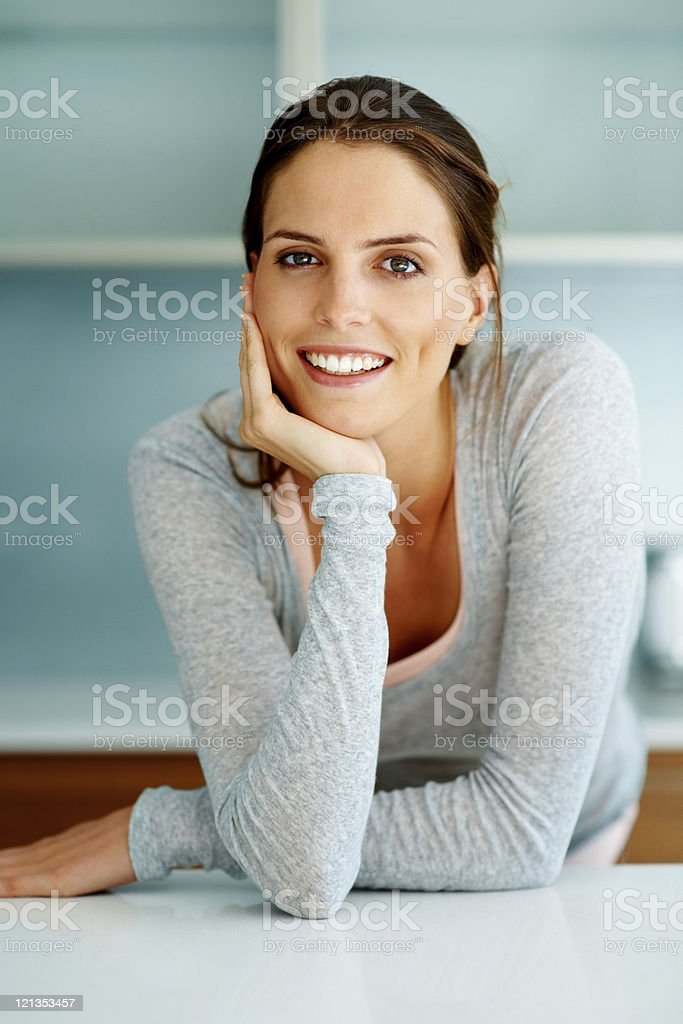 Smart young woman standing at the kitchen counter stock photo