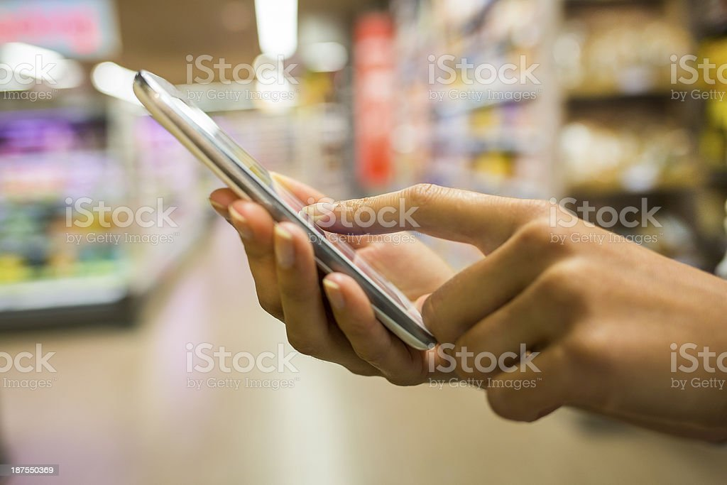 Smartphone and hands with supermarket background stock photo