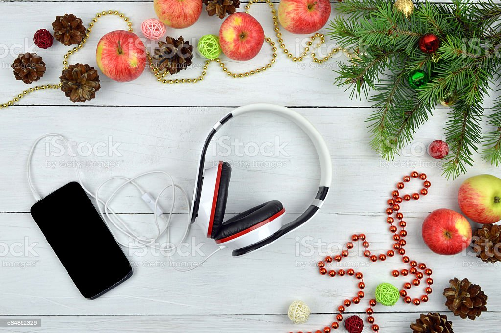 Smartphone and headphone  with rustic Christmas decorations. Christmas melodies. stock photo
