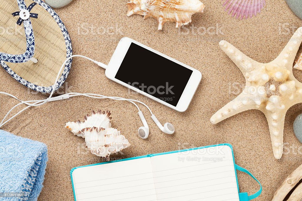 Smartphone and notepad on sea sand with starfish and shells stock photo