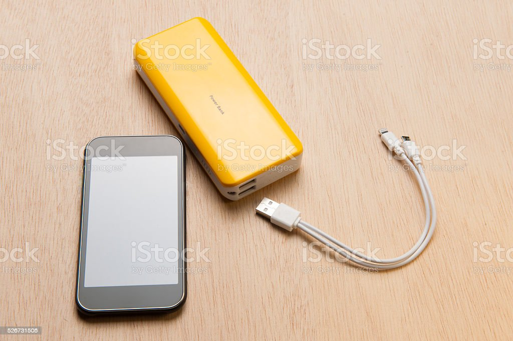 Smartphone and powerbank on wooden table stock photo