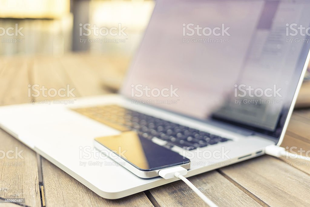 Smartphone being charged by a laptop stock photo