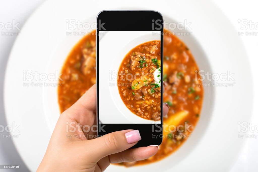 Smartphone camera hand point shoot photo soup. Food photograph. Made for social networks stock photo