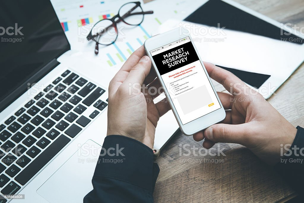 Smartphone in hand and filling Market Research Survey concept stock photo