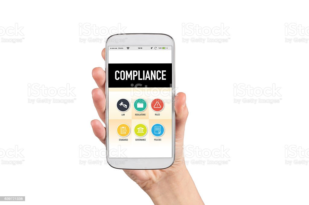 Smartphone in hand and showing Compliance concept on screen stock photo