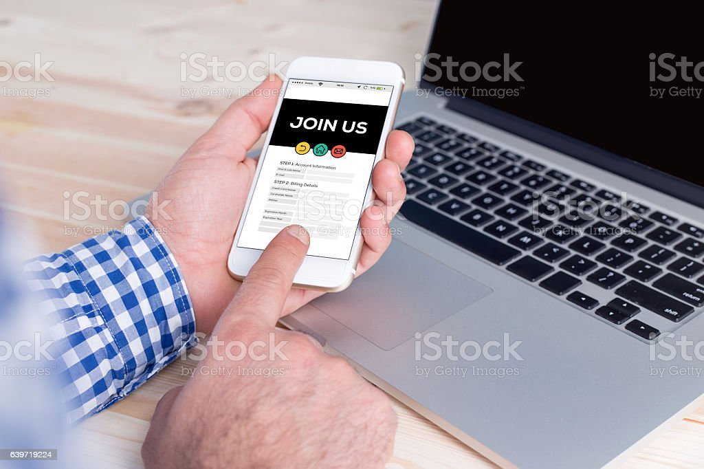 Smartphone in hand and showing Join Us concept on screen stock photo