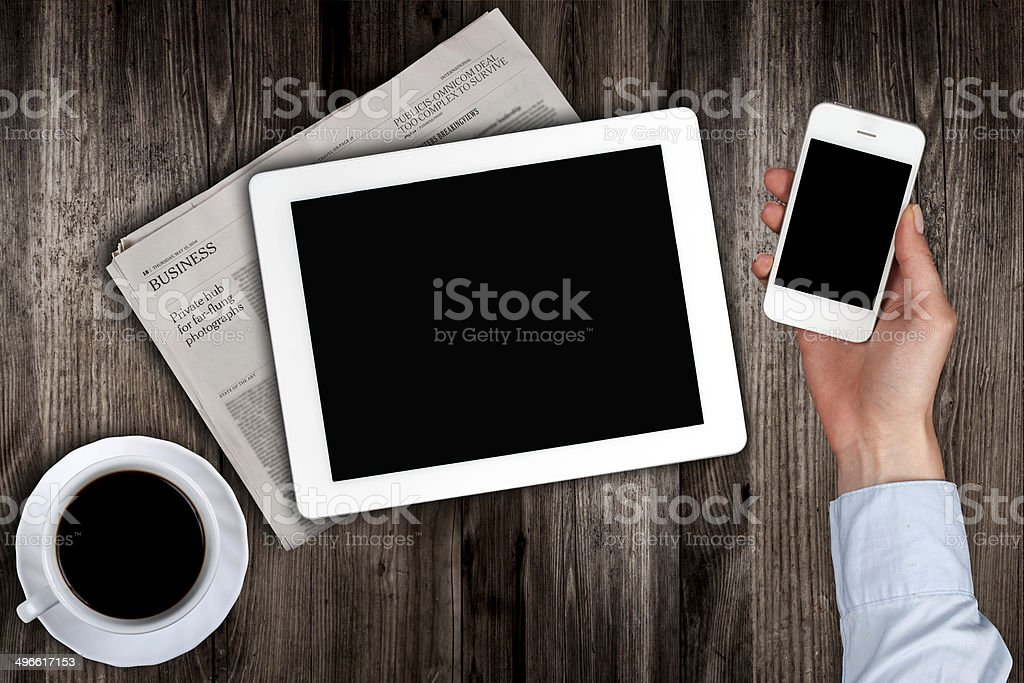 smartphone in hand  with the tablet on the table stock photo
