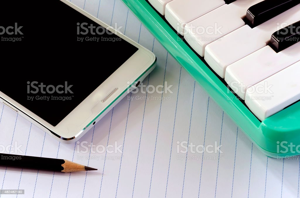 Smartphone melodica and pencil stock photo