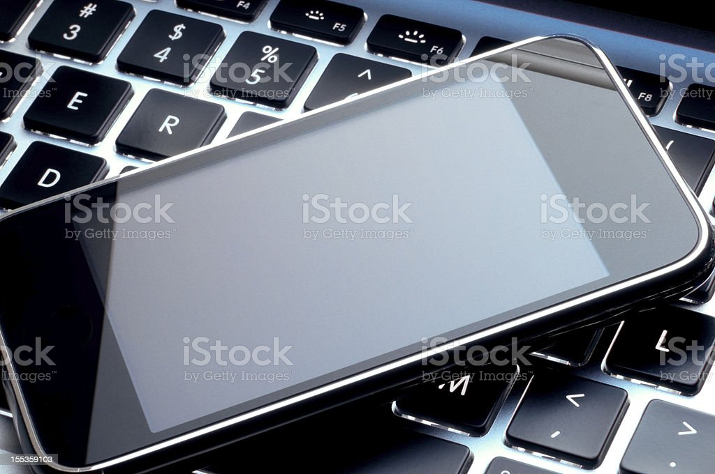 Smartphone on top of a laptop representing technology royalty-free stock photo