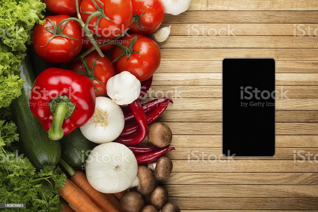 Smartphone on wooden surface with fresh vegetable mix royalty-free stock photo