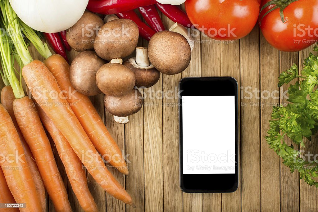 Smartphone on wooden surface with vegetables royalty-free stock photo