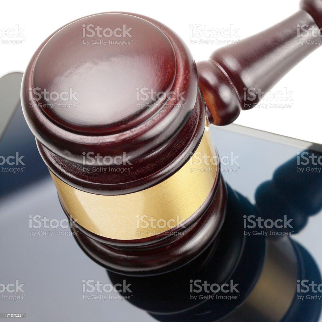 Smartphone under judge gavel - close up studio shot stock photo