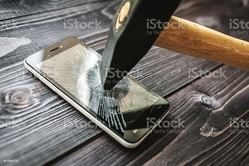 Smartphone with broken display on the wooden rustic background stock photo
