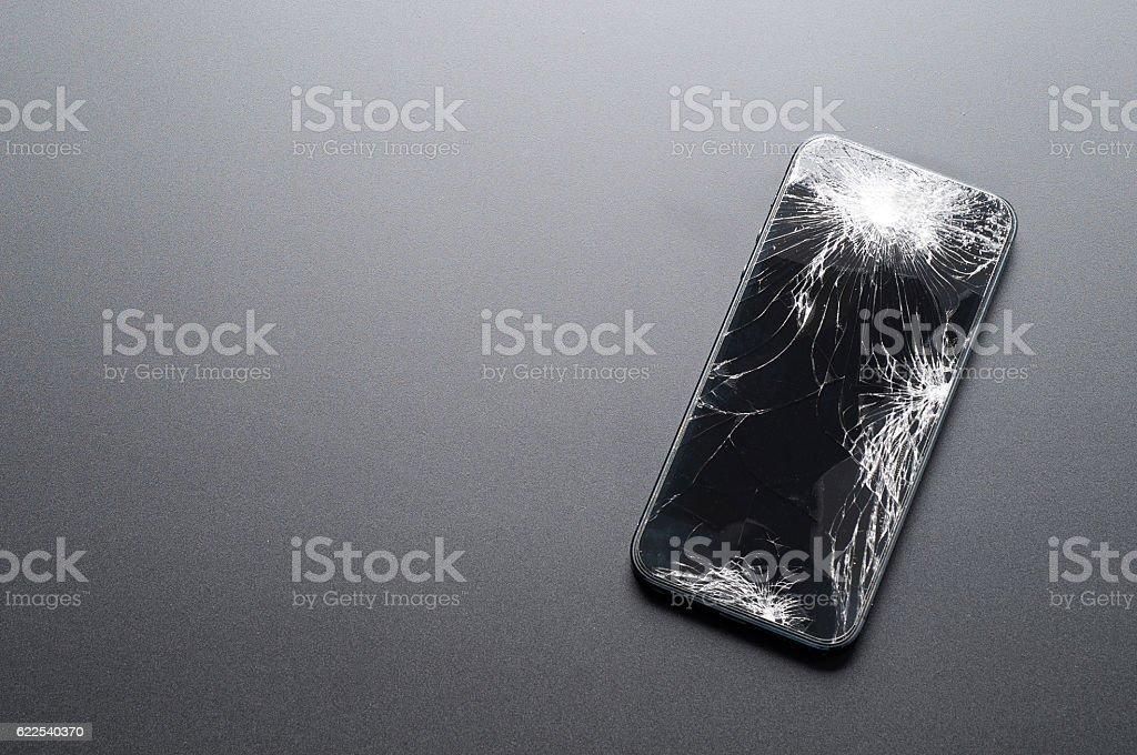 Smartphone with broken screen on dark background stock photo