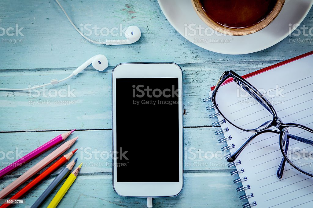 Smartphone,cellphone,notebook,pencil color,glasses and coffee stock photo