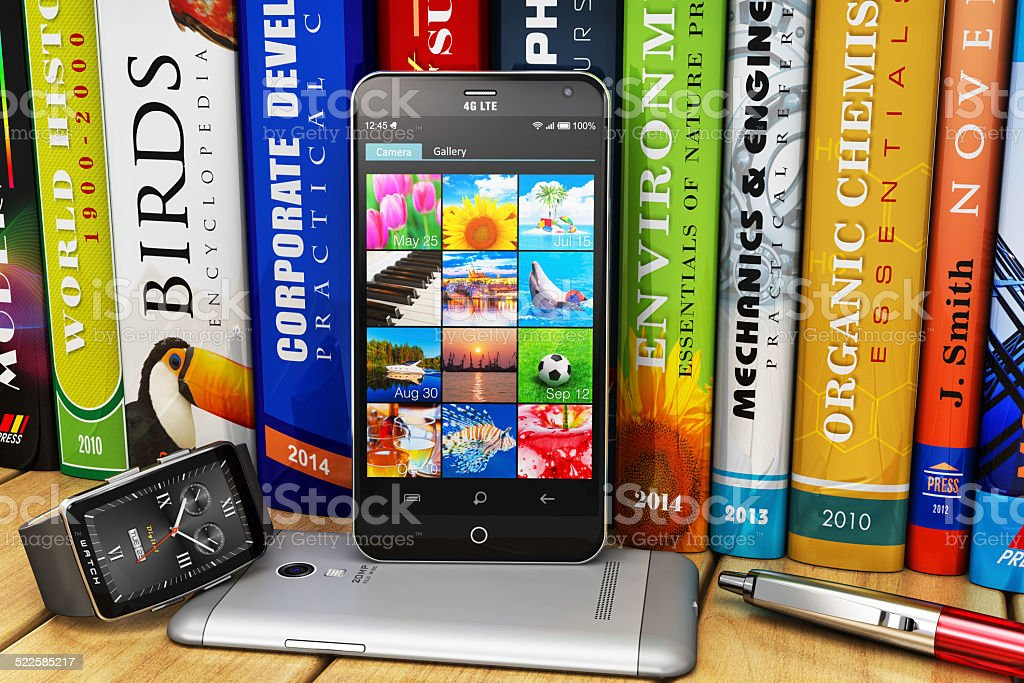 Smartphones and smartwatch on bookshelf stock photo