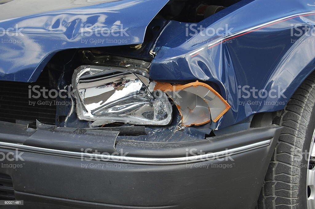 Smashed headlight on blue car stock photo