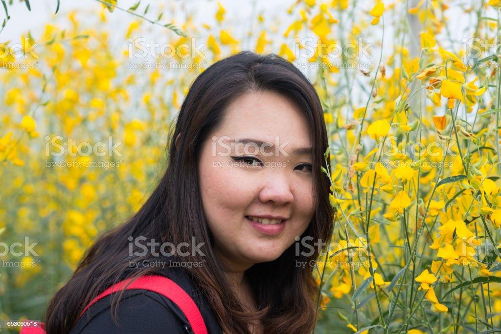 Smile Beautiful Asian fat woman in yellow flower garden stock photo
