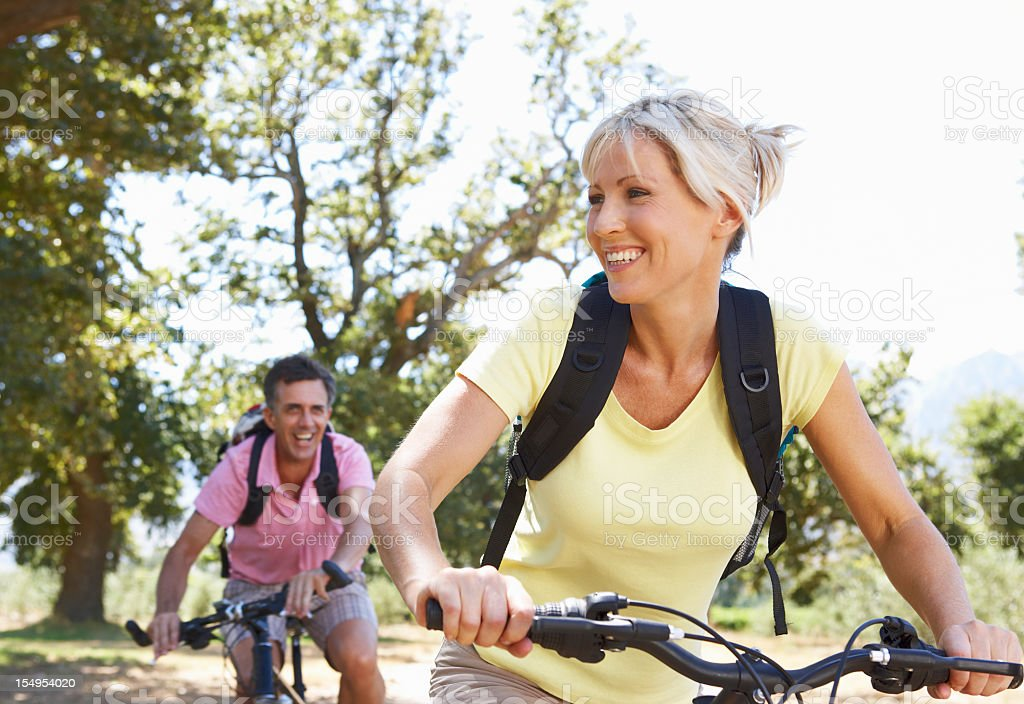 A smile middle aged couple bicycling through the countryside royalty-free stock photo