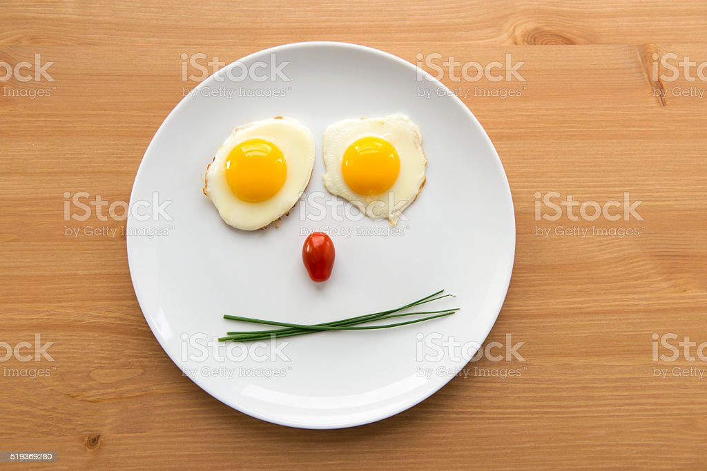 smiley breakfast plate with eggs, tomatoes and ham stock photo