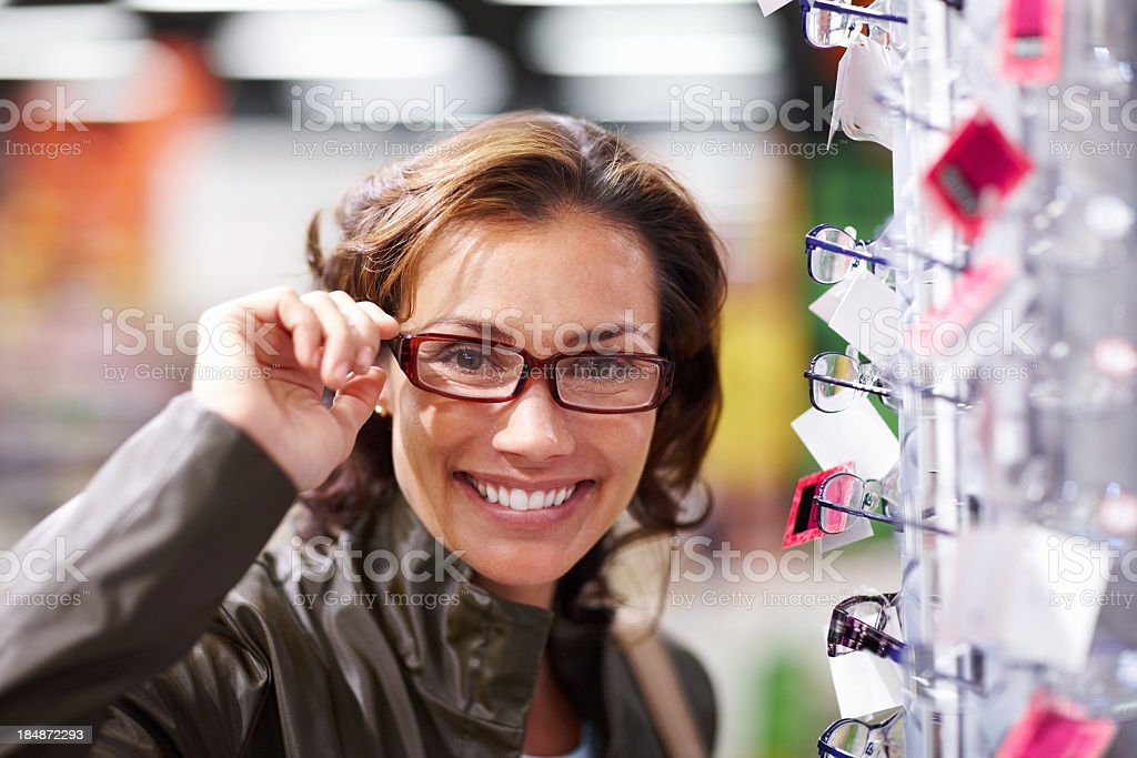 Smiley brunette woman trying new glasses royalty-free stock photo